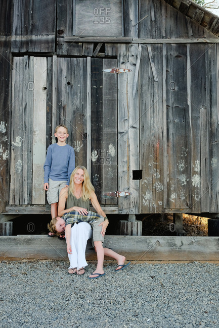 Mother and two sons in front of old wooden barn
