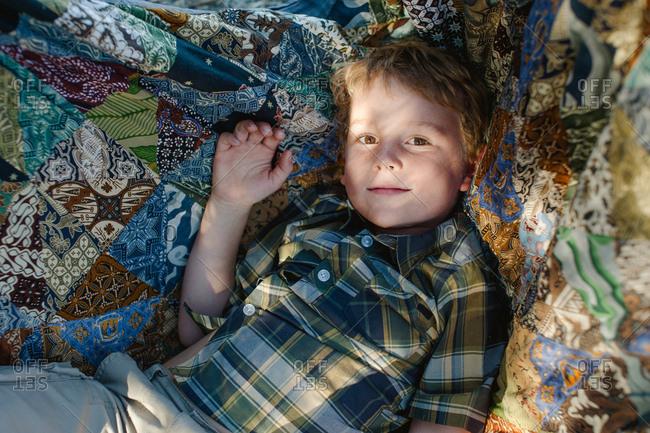 Little boy lying on blanket on ground