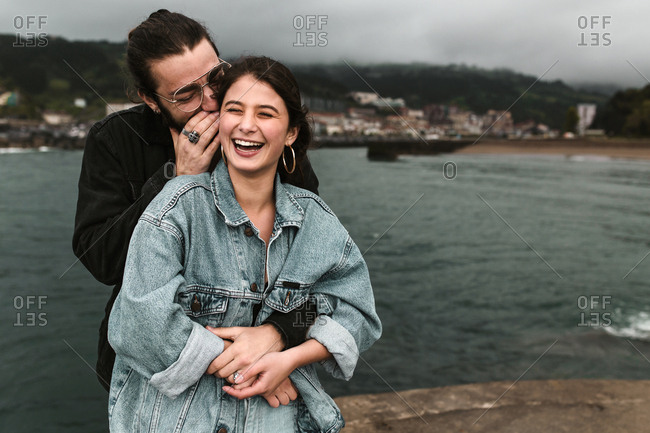 Young man with glasses whispering exaggeratedly to female partner on gloomy beach day