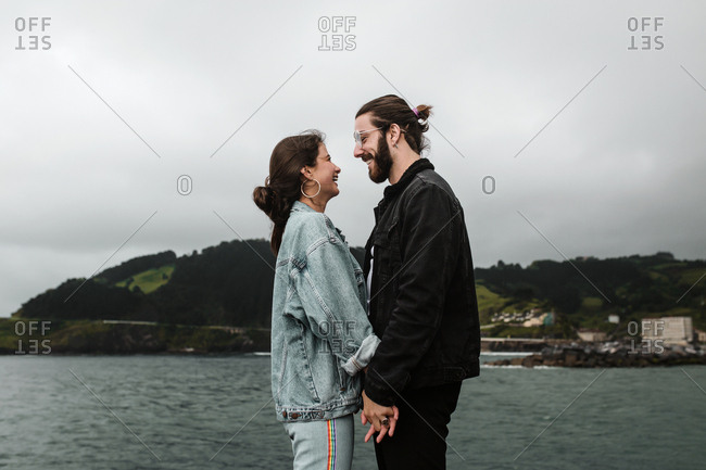 Brunette man and woman clasp hands facing each other in front of beach hillside view
