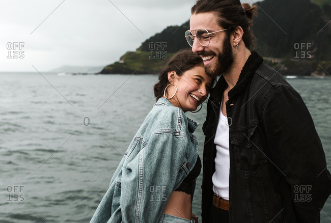 Young quirky couple share a candid laugh at the stormy beach