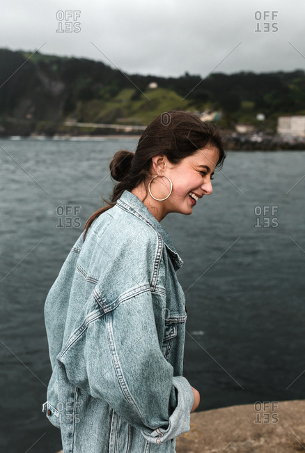 Profile of young woman in deep laughter on overcast day at the coast
