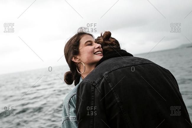 Happy girlfriend smiling over boyfriend's shoulder on beach trip