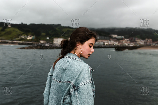 Contemplative brunette woman in vintage denim jacket before stormy weather at the beach
