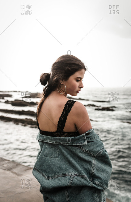 Lonely woman looks over shoulder in silence on overcast beach day trip