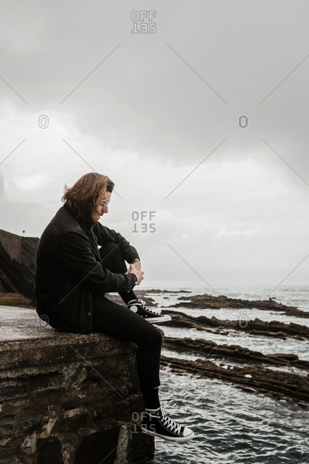 Moody brunette man sits quietly on corner of stone wall