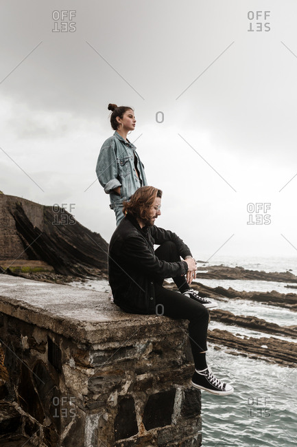 Young adult couple hanging out on rock wall at the beach