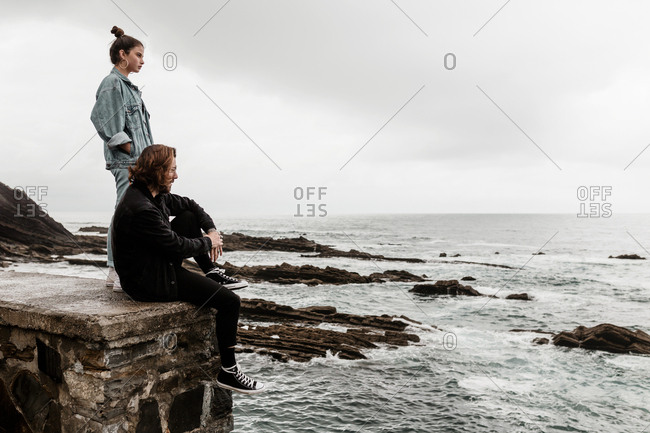 Stylish man and woman watching dreary beach on a dark afternoon