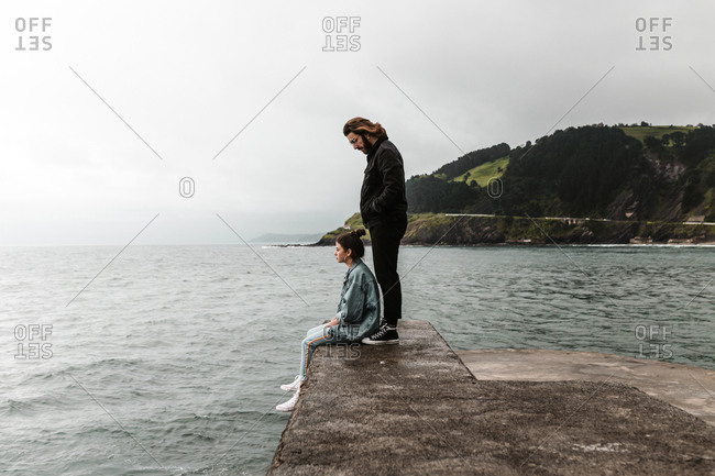 Boyfriend standing behind girlfriend sitting on cement ledge watching ocean view