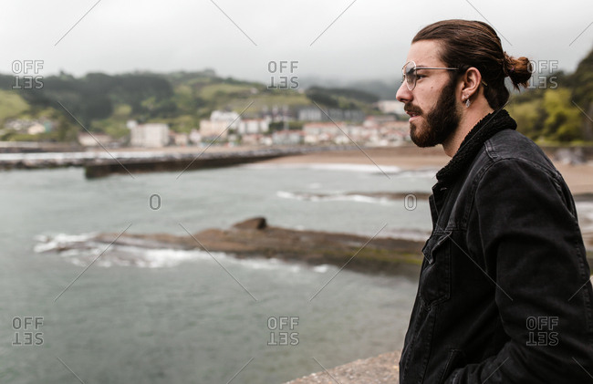 Bearded young man in dark jean jacket at the beach staring across stormy water