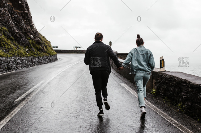 Flighty young couple running towards winding mountain road wall in the distance