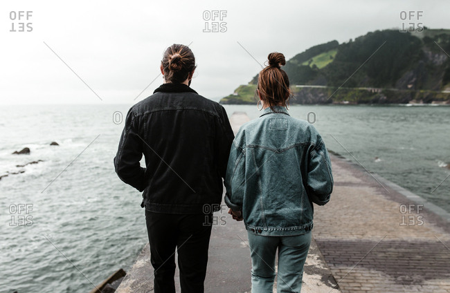 Back view of young adult couple walking along stone pier together