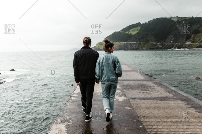 Stylish young couple walking and looking around seaside pier