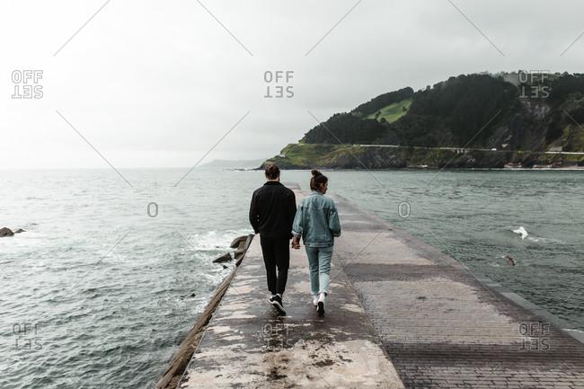 Carefree tourist couple in in coordinated denim strolling along rough coastal pier near dusk