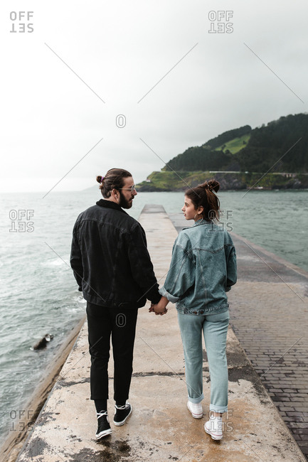 Young romantic interests share a glance while walking hand and hand along seashore platform