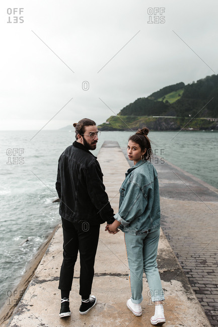 Brunette couple looking over shoulders at camera paused on beach walk