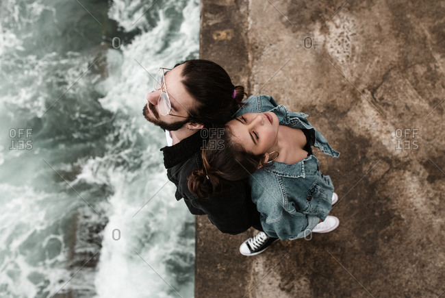 Overhead view of brunette couple standing back to back near ocean drop off