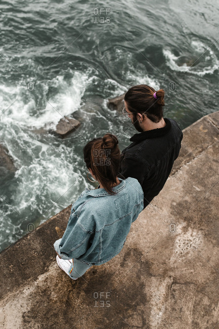Daring couple standing at edge of tall platform watching ocean waves splash below
