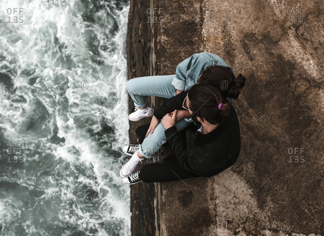 Young couple sitting together with legs dangling over crashing sea waves below