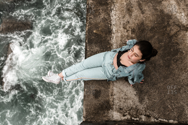 Solitary female sitting silently over beach ledge in vintage denim outfit