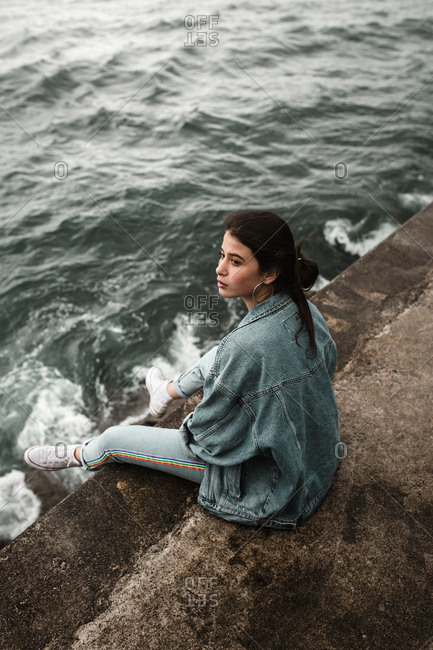 Brunette model in retro jean outfit looking over shoulder above murky sea tide