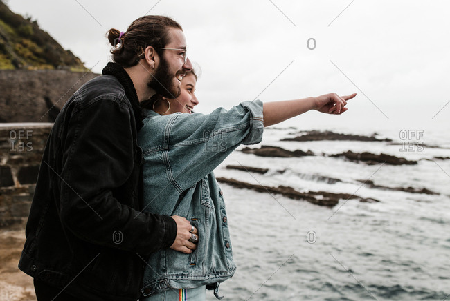 Girlfriend pointing into the distance on beach date with boyfriend