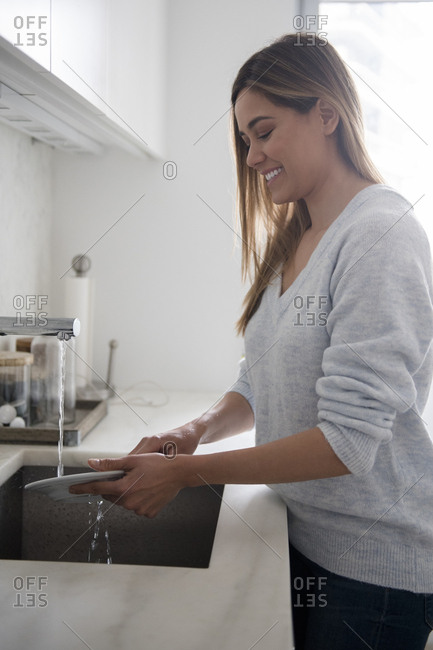 Young woman doing dishes in kitchen