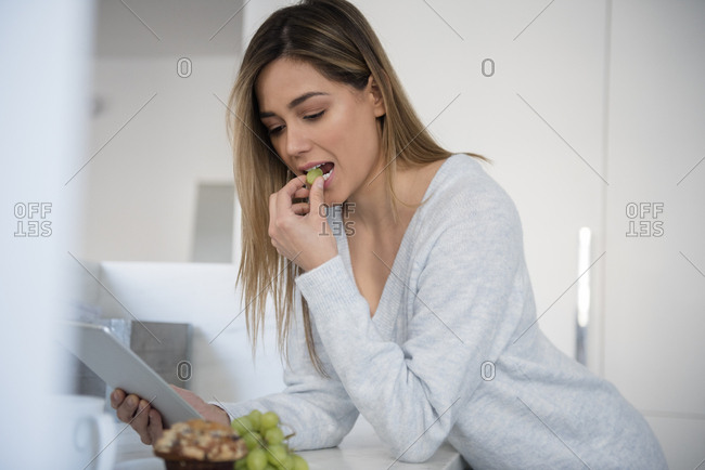 Young woman eating white grapes and using digital tablet