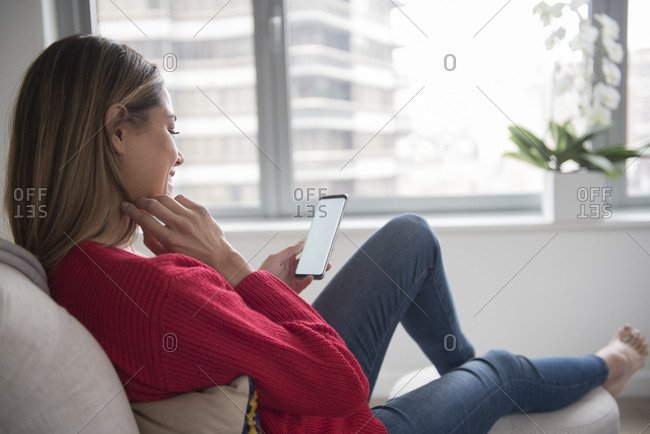 Young woman using smart phone in living room