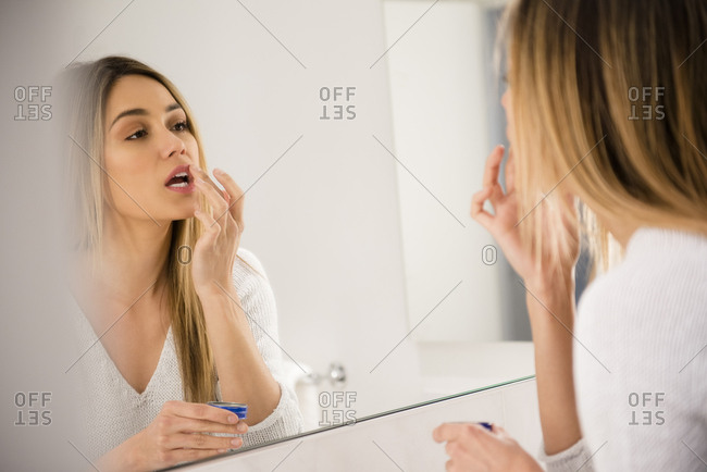 Young woman looking in mirror and applying lip balm