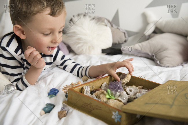 Little boy (4-5) with box full of treasures