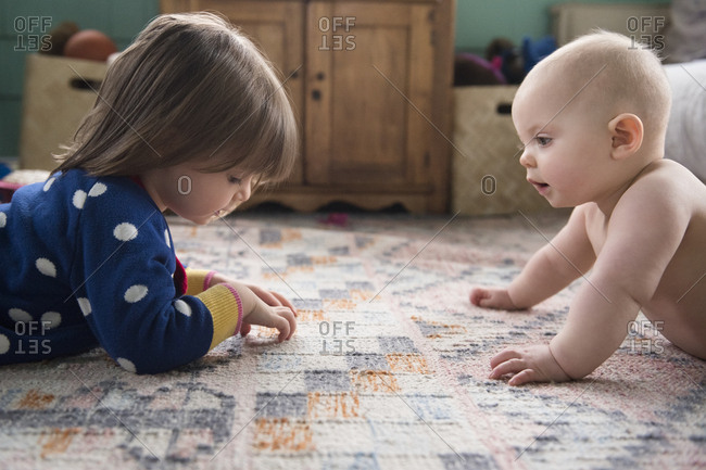 Sisters (12-17 months, 2-3) playing on carpet