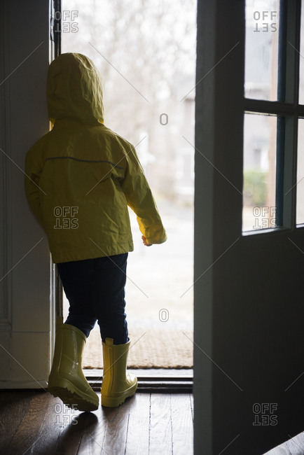 Girl (2-3) in rubber boots and rain cape standing at open door