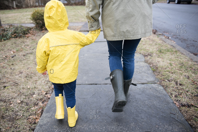 Mother and daughter (2-3) holding hands and walking on rainy day