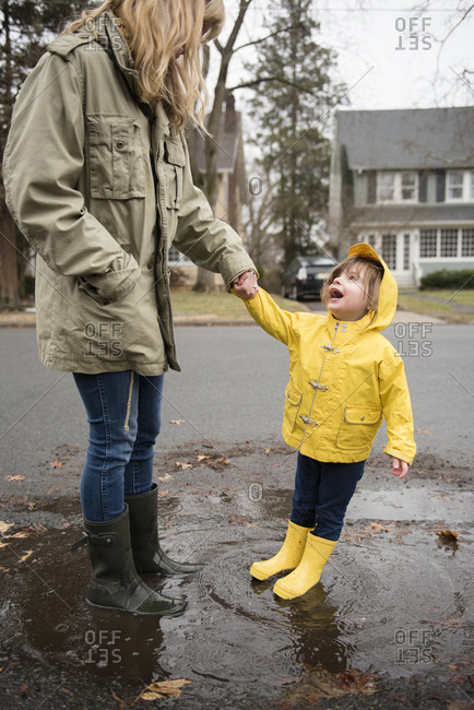 Mother and daughter (2-3) in puddle