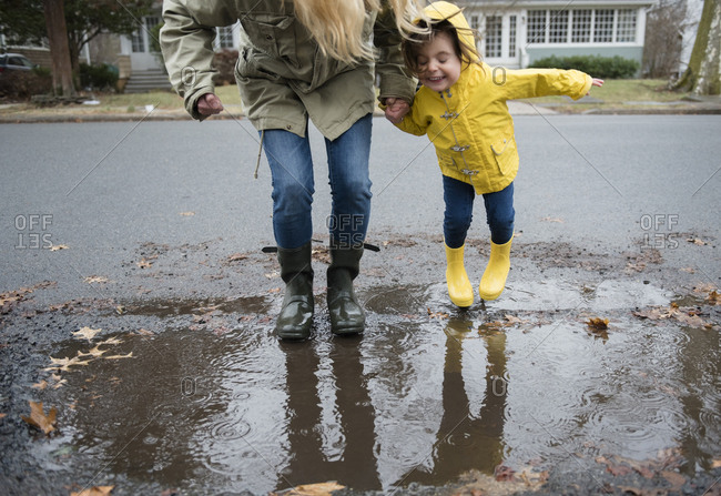 Mother and daughter (2-3) near puddle