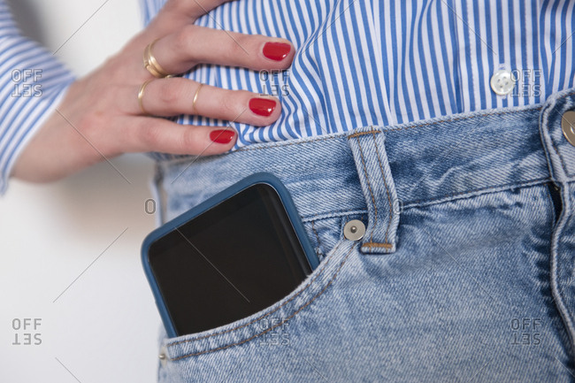 Woman with smartphone in jeans pocket