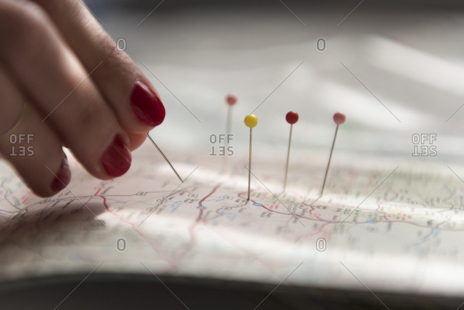 Woman applying pins on map