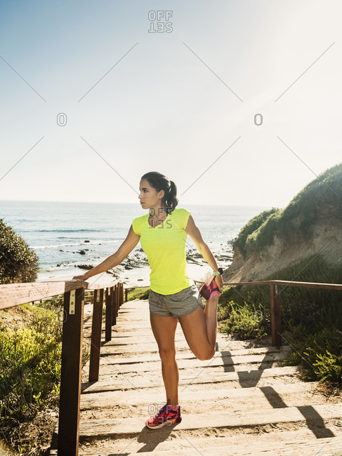USA, California, Newport Beach, Woman stretching on beach