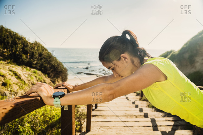 USA, California, Newport Beach, Woman stretching on beach