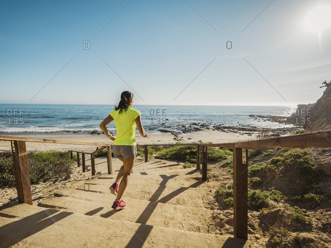 USA, California, Newport Beach, Woman running down stairs