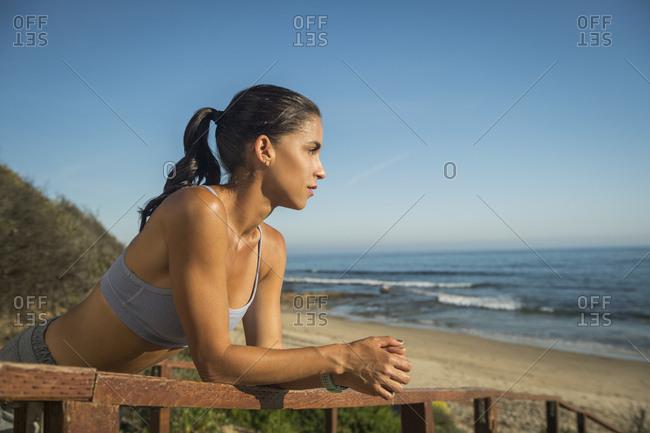 USA, California, Newport Beach, Woman in sport suit looking at sea