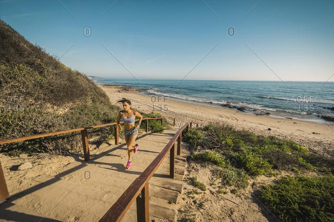 USA, California, Newport Beach, Woman running up stairs