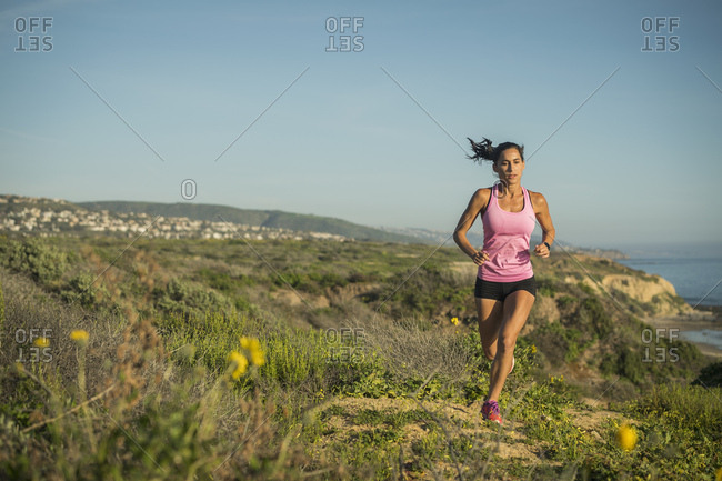 USA, California, Newport Beach, Woman running along cliff