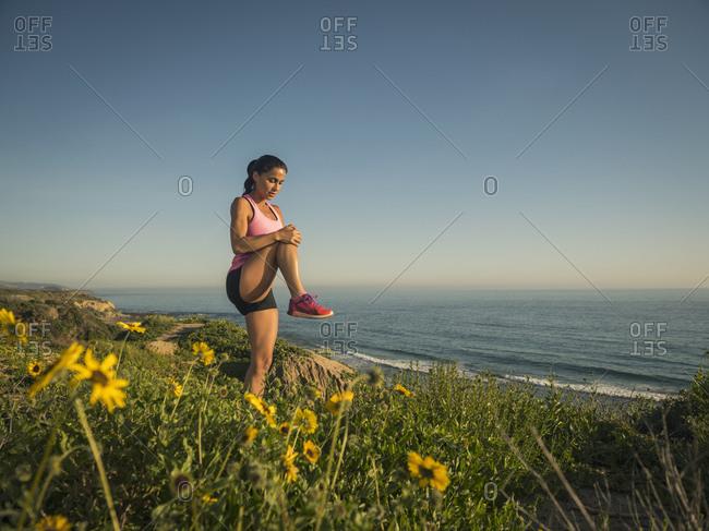 USA, California, Newport Beach, Woman stretching on cliff