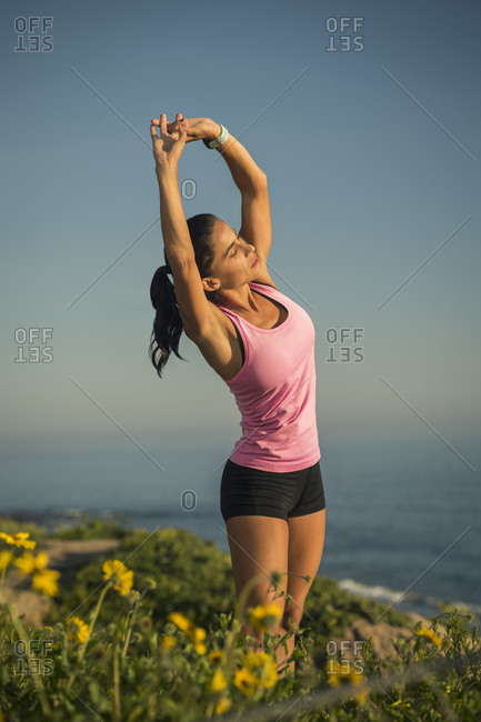 Woman stretching against blue sky