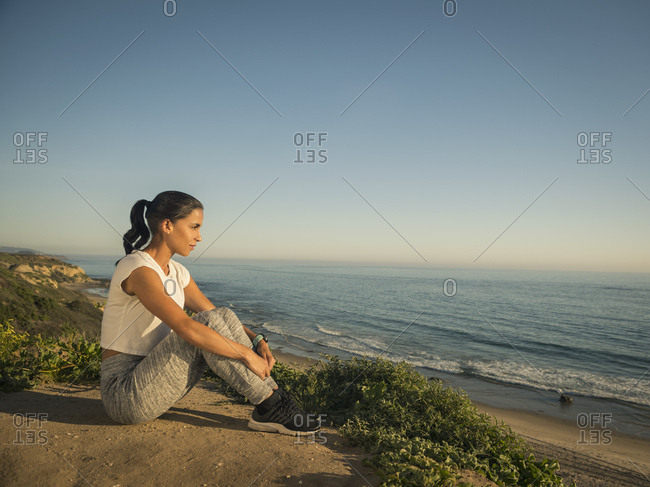 USA, California, Newport Beach, Woman in sport suit sitting on cliff and looking at view
