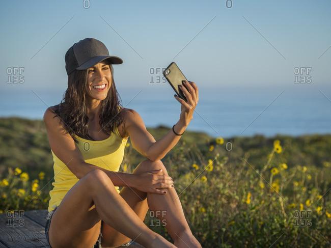 Woman in baseball cap taking selfie