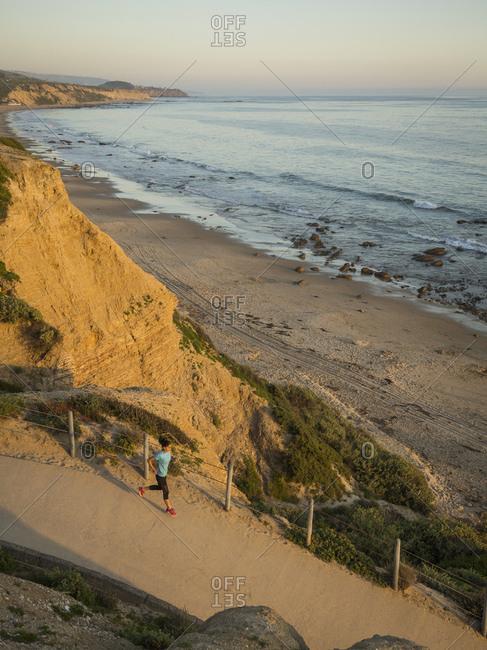 USA, California, Newport Beach, Woman running along footpath