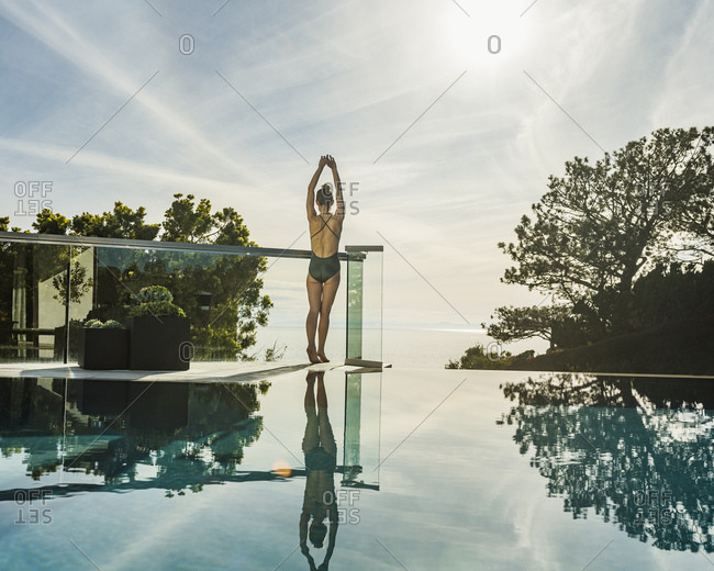 Woman stretching by swimming pool